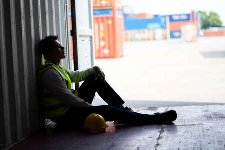 Factory worker man sit in the cargo container and he look tire and lost job. Concept of good system and manager support for better industrial business.