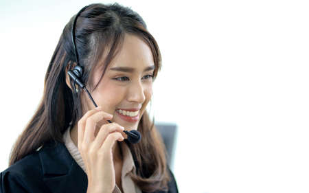 Smiling female customer support operator with headset working in office, Asian young woman working in call centre. Imagens