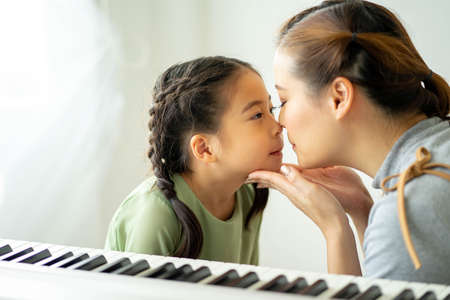 Happy loving family, Mom and daughter playing and kissing, Togetherness concept.