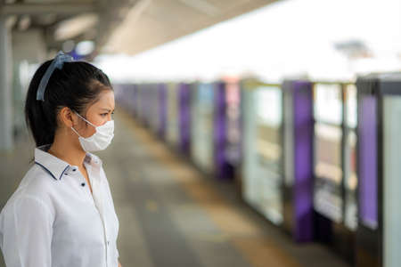 A woman standing with a mask on a train station.