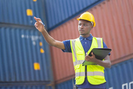 American African Engineer or supervisor checking and control loading Containers box from Cargo at harbor. Transportation and logistic concept. Imagens