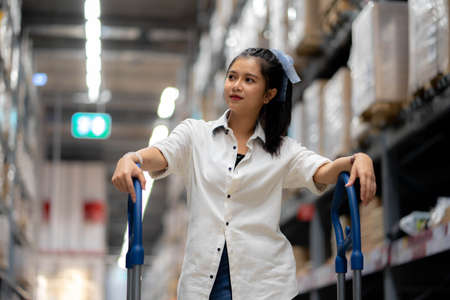 Asian woman with shopping cart walking for choosing new furniture in big store warehouse.