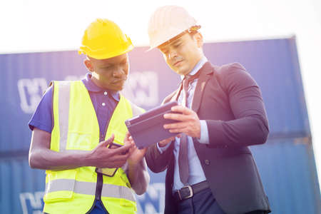 Construction worker pointing on architectural plans and architect, Engineer Concept. Imagens