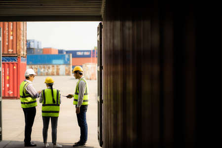Team engineer dock control logistics worker wear safety helmets and protect suite open cargo container door and working and checking product with taplets.