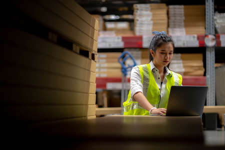 Woman warehouse Staff Check stock details on tablet computer for checking goods and supplies on shelves with goods background in warehouse, logistic and business export.