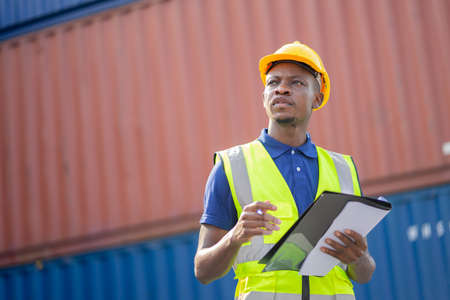 American African engineer or factory worker man working  at Container cargo harbor to loading containers. African dock male staff for Logistics import export shipping concept.