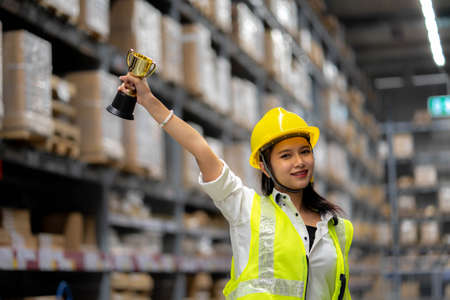 Happy smiling woman warehouse Staff holding a trophy after being selected as an outstanding employee Imagens