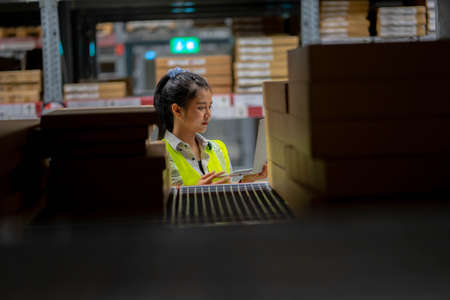 Asian engineer woman Check stock details on tablet computer for checking goods and supplies on shelves with goods background in warehouse, logistic and business export.