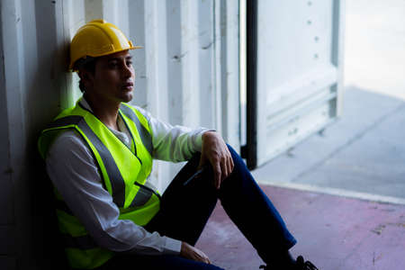 Factory worker man sit in the cargo container and lost job. Concept of good system and manager support for better industrial business. Imagens