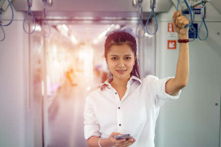 Young Asian Woman using mobile phone in sky train car, leisure and daily life.
