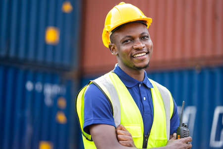 American African engineer or factory worker man at Container cargo harbor to loading containers. African dock male staff for Logistics import export shipping concept.
