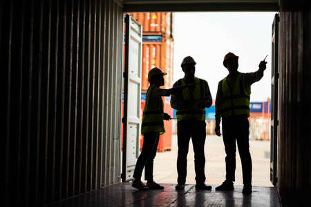 Silhouette of Team engineer dock control logistics worker wear safety helmets and protect suite open cargo container door and working and checking product with taplets.
