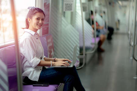 Asian young woman using a notebook on the sky train, leisure and daily life.