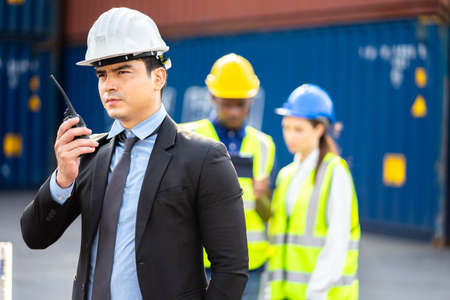 Builder Engineering in hardhat with radio communication over group of builders at construction site. Imagens