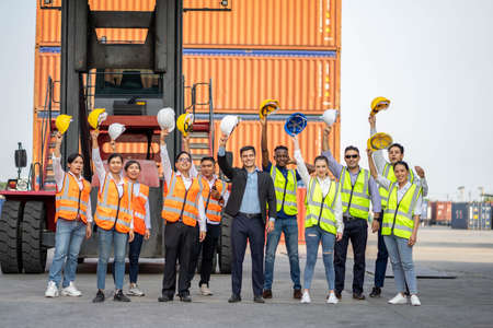 Group of employees and management team wearing logistic uniforms and stand to celebrating or raise their hands together for exporting products abroad. Finishing successful.
