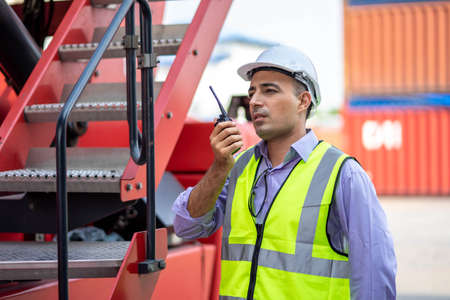 A male engineer or manager Use of radio communication to control container load in industrial transport and logistics concepts.  business, building, industry. Imagens
