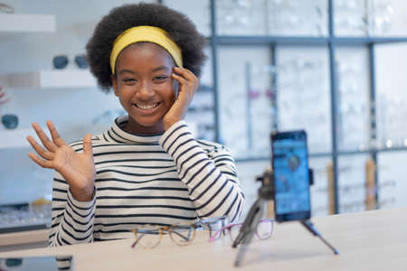 Smiling pretty african teen girl blogging online and streaming live. African teenage girl use social media for business at home. New normal lifestyle and Social Distancing.