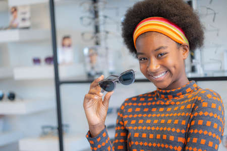 Smiling pretty african teen girl holding new Sunglasses frames in an optician store. Imagens