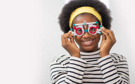Happy Young black woman checking vision with eye test glasses during a medical examination at the ophthalmological office, ophthalmology concept. Standard-Bild