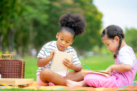 Two children lying and drawing with colored pencils at summer park, feel happiness, friendship and Happiness people, outdoor education concepts.