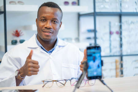 Ophthalmologist doctor african american entrepreneur is vlogger or Blogger show new fashion glasses to cellphone online live streaming in eyeglasses shop.
