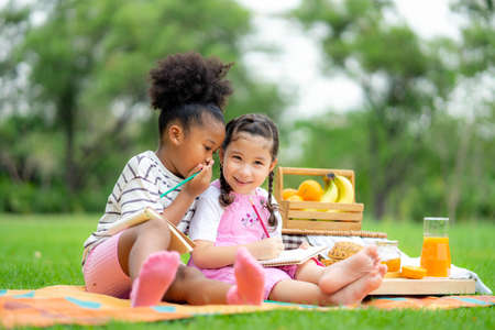 Two Happy kids relaxing on picnic in summer park and whispering. Healthy lifestyles concept.