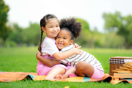 Two happy girls as friends hug each other in cheerful way. Little girlfriends in park. Childhood, family, love, friendship and Happiness people concept Standard-Bild