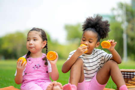 Two little happy children sitting on the plaid, eating oranges fruits and looking at each other in the park in warm autumn day.