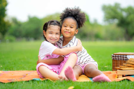Two american african little girl as friends hug each other in cheerful way. Little girlfriends in park. Childhood, family, love, friendship and Happiness people concept Standard-Bild