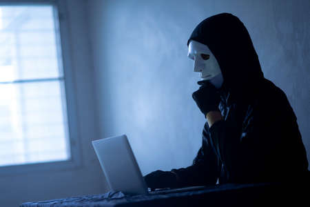 Hacker with computer man hidden face in the dark, Data thief, cyber crime concept. darknet and cyber security concept.