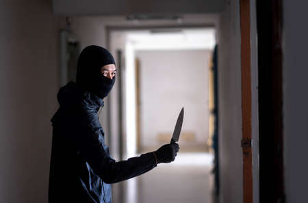 Murder wear the mask holding a knife and Standing in the old apartment, kill and people concept - Criminal or murderer with blood on knife at crime scene. Standard-Bild