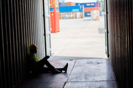 Silhouette of Factory worker woman sit in the cargo container and he look tire and lost job. Concept of good system and manager support for better industrial business. Standard-Bild