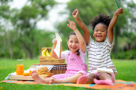 Happy children playing in summer park on warm sunny fall day. Healthy lifestyles concept.