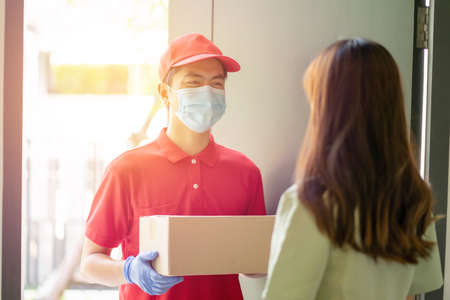 Deliver man wearing face mask in red uniform handing a parcel box over to a customer in front of the house. Postman and express grocery delivery service during covid19.
