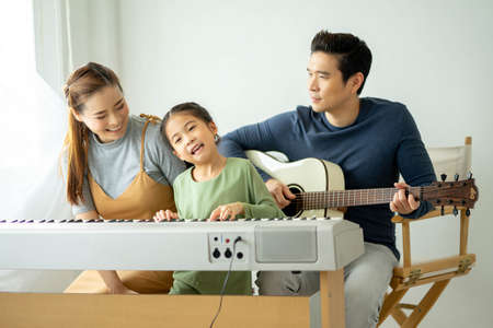 Happy little Asian family daughter playing piano with mother and father play guitar at home, Mother teaching daughter to play piano,They play and sing songs. concept for family relationship.