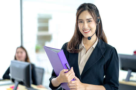 Asian young woman working in call centre. Young friendly operator woman agent with headsets working in a call centre.