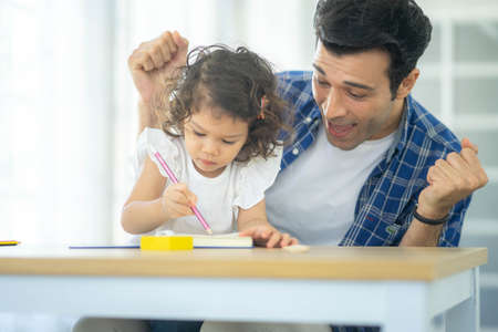 Happy family: Father teaching his cute little daughters' study. Family creativity and education at child's room, home schooling concept.