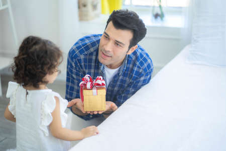 Handsome young father is giving a gift box to his cute little daughter, Love family day parenthood childhood concept. Standard-Bild