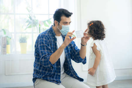 Father helping her daughter to wear a mask, both are wearing face masks for confidence in their health. Protect themselves from dangerous spread of coronavirus covid-19.