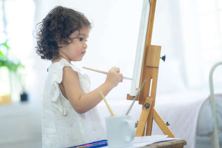 Adorable little girl painting art in the living room, a child learn painting at home.