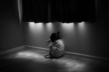 Squat single child sit near window, sad lonely in dark night indoor, crying, bad mood, offended, consoles,  concept of unhappy childhood, life together Standard-Bild