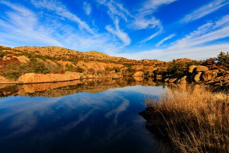 The sky and rocky edge reflects in the still water in the early morning at Wichita Mountains National Wildlife Refuge, November 2017