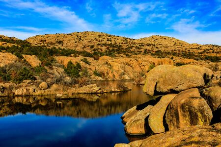 Rugged landscape meets smooth water as it winds between the rock at Wichita Mountains National Wildlife Refuge Stock Photo