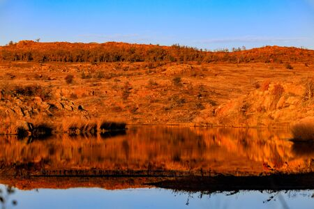 Red morning sun cast light refleting the orange glow in water at Wichita Mountains National Wildlife Refuge, November 2017 Editorial