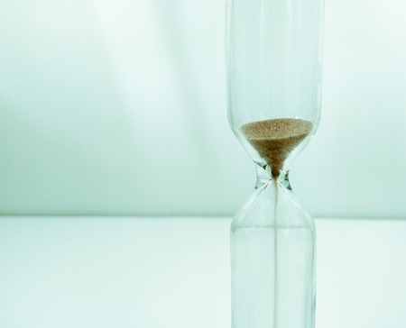 Sand running through the bulbs of an hourglass Banco de Imagens