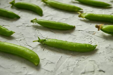 many of Green Pea Pods on factured surface.
