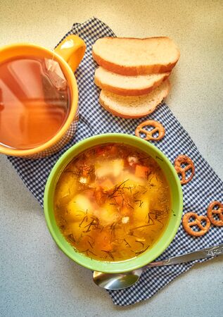 The usual home-made lunch. A Cup of soup with potatoes, carrots and beef. green tea and mini-brezel. Pieces of loaf