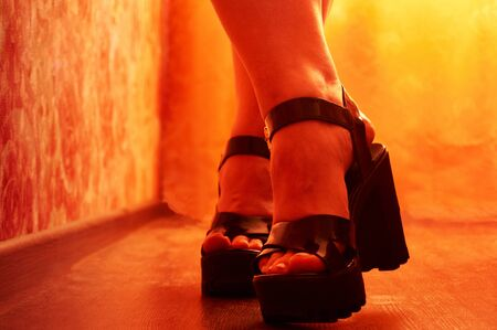 Close up of woman leg in black shoes. Close up of woman leg in black shoes. A woman's foot in shoes with a high platform and a large heel. Rich orange lighting.