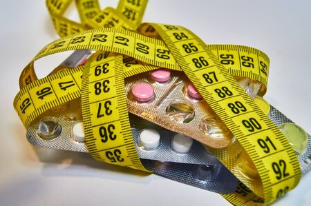 Pills with measuring tape, represent the diet pill industry. concept of losing weight, diet, fat burning, healthy eating.