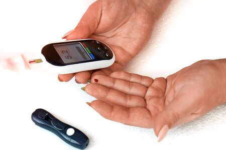 Un diabético controla su nivel de azúcar en sangre. La mujer se autoevalúa con una lanceta y un glucómetro en casa. Ver resultados
